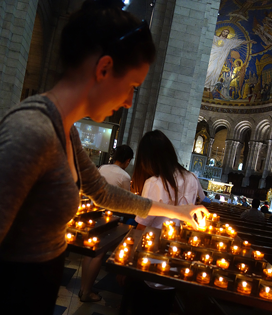 Lighting a candle at Sacre Coeur